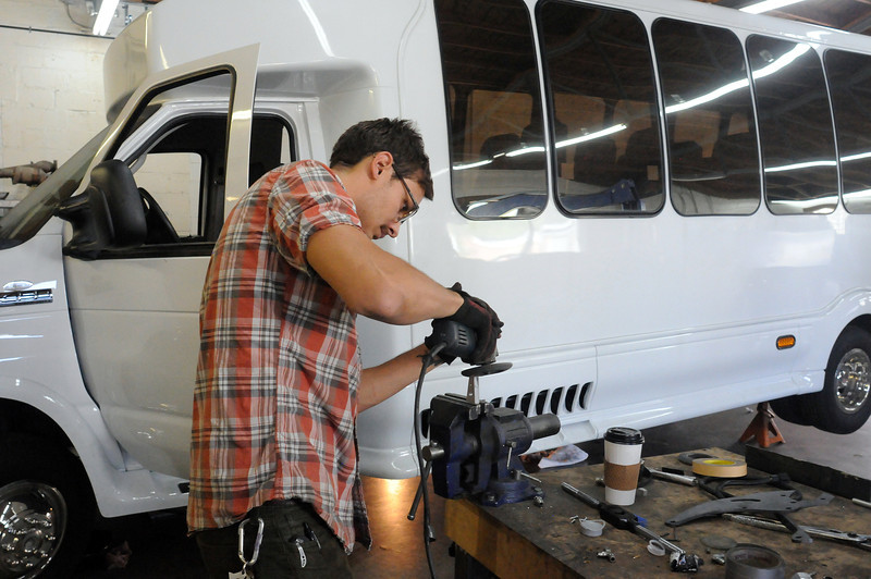 Ian Patterson, a mechanical engineer with Lightning Hybrids, works Wednesday on a piece of the brake pedal system for the shuttle bus behind him. The bus, outfitted with the Loveland company's hydraulic power technology, is headed for a major bus-industry convention in Chicago next week. (Photo by Craig Young)