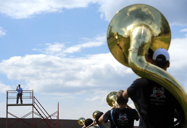 Kyle Freesen, new band director at Loveland High School, leads the marching band, the Crimson Regiment, during practice on Thursday at the school.