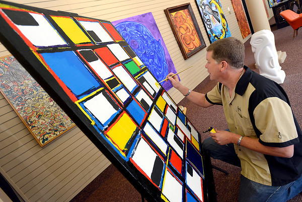 Artist Jade Windell works on a painting Thursday at the old Mr. Neats space in downtown Loveland. The space, which is owned by the city, is being used as a studio and gallery with alternating artists who will use it on a quarterly basis. Windell is the first artist chosen to use the space.