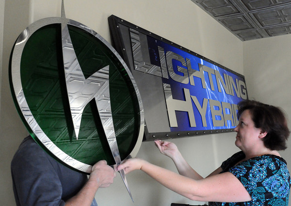 Bonnie Trowbridge, vice president of marketing and business development for Lightning Hybrids, helps employee Ted O'Brien remove the company logo from a sign in preparation for next week's BusCon event in Chicago. (Photo by Craig Young)