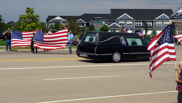 Windsor residents display American flags as the hearse carrying the body of Staff Sgt. Christopher Birdwell drives near his boyhood home Friday.