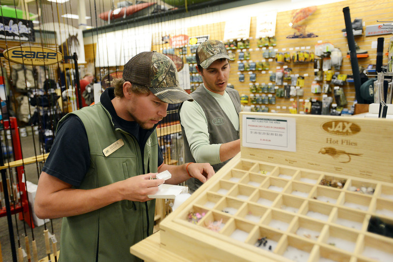 Jax Outdoor Gear fishing department sales associate Hayden Spencer, left, and department manager Casey Prather stock flies on Friday, Sept. 21, 2012 at the store's Loveland location at 950 E. Eisenhower Blvd.