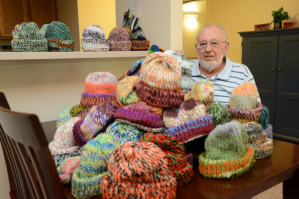 Robert Schmidt poses Tuesday, Sept. 11, 2012 in his Loveland home by some of the caps he's knitted to be donated to indigent children in Texas.