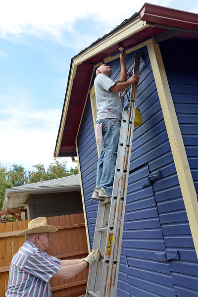 Golden K Kiwanis member Jake Jacobson, left, holds the ladder steady while Tyler Rusch with Big Thompson Kiwanis paints the soffit on a garage while volunteering during the Paint Our Town event in the 600 block of Harrison Avenue in downtown Loveland.