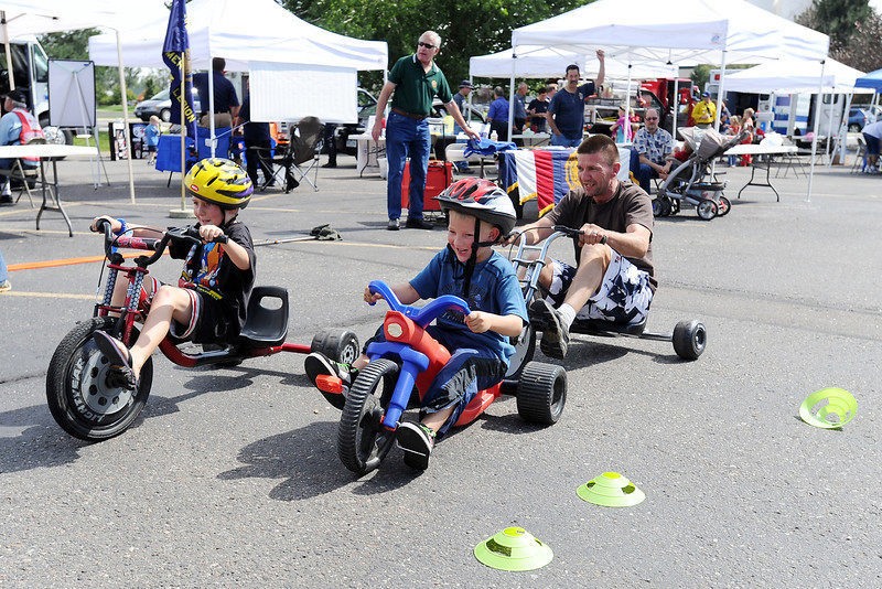 Koda Sterling, 9, left, and his brother Kiau Sterling, 6, pull ahead of their dad Rick Sterling while racing each other on big wheel trikes during the Emergency Preparedness and Family Safety Expo on Saturday, Sept. 15, 2012 in the parking lot at Jax Mercantile Co., 950 E. Eisenhower Blvd. The third annual safety event featured a variety of booths and demonstrations including a fire safety trailer, railroad crossing safety display, Colorado State Patrol  vehicle roll-over simulator, bike helmet fit testing, free child ID kits and a display of emergency vehicles.
