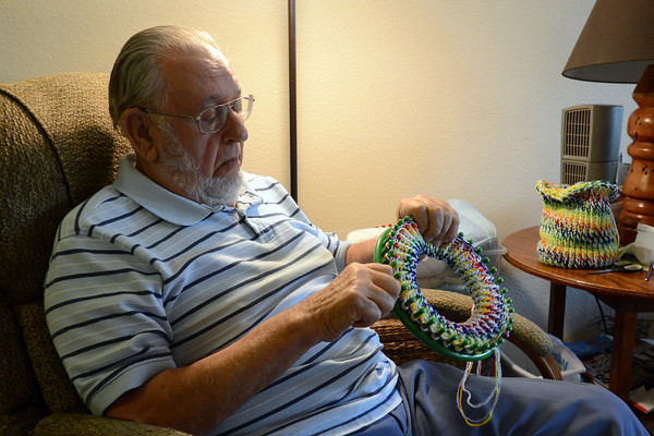 Robert Schmidt works on a knitted cap on Tuesday, Sept. 11, 2012 in his Loveland home. Schmidt has knitted thousands of hats over the years that he donates to needy children.