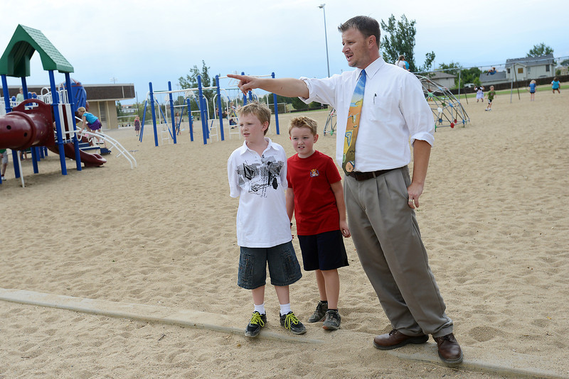 Ivy Stockwell Elementary School principal Rick Bowles chats with third-graders Jered York, 9, left, and Max Goodrich, 8, while on duty during recess Thursday, Aug. 30, 2012 on the school's playground.