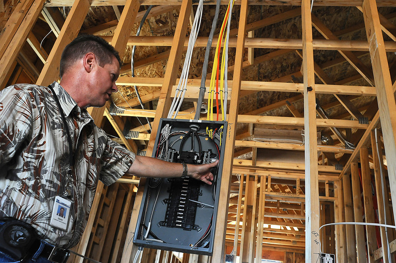 City of Loveland Building Inspector Dave Sprague inspects electrical wiring on Wednesday at a Habitat for Humanity home in the 2000 block of Sagittarius Drive in Loveland.