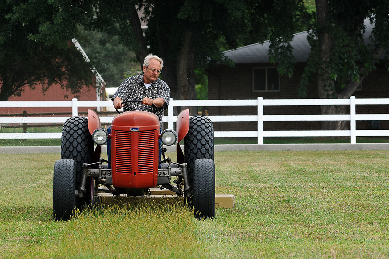 Doug Gertsch mows a lawn on his land just southeast of the intersection of South Taft Avenue and West Eighth Street on Sunday. To mow all of the grass it takes him about half of a day but he says he enjoys the relaxing work.