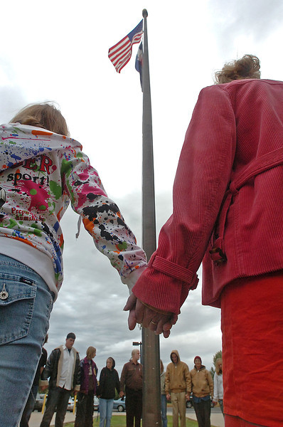 "Thompson Valley High School student Hanna Hardy, 14, left, and her mother Monika, right, a math teacher at the school, hold hands as they pray with other students around the flagpole Wednesday morning before school as part of the annual ""See You at the Pole"" event."