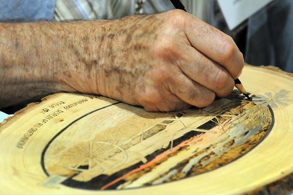 Harold Nickerson of Fort Collins darkens areas of a wood burning he did of a wagon on his grandfather's homestead near New Raymer while at the Northern Colorado Wood Carvers 17th annual Show, Sale and Competition on Sunday at The Ranch.