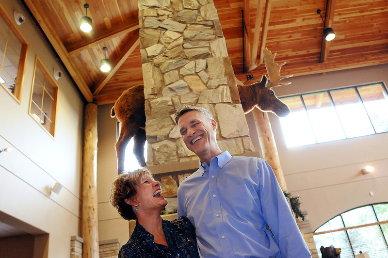 Thom and Joani Schultz, owners of Group Publishing, pose in front of Bruce the Moose on Monday at in the company's lobby. Group Publishing, which produces and distributes products for Christian ministry, will celebrate 35 years on Sept. 28.