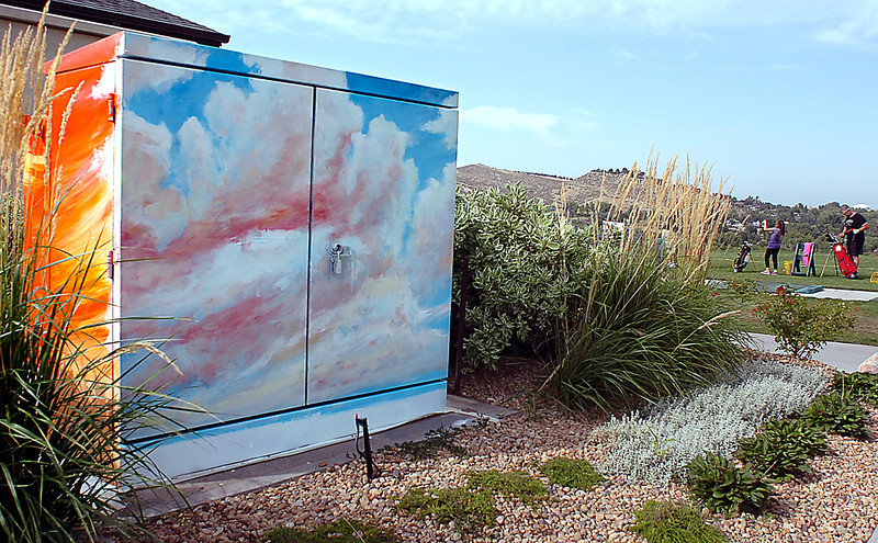 "One of the recently painted transformer boxes adds to the scenery at Mariana Butte Golf Course as Mike Terpstra and his granddaughter, Ashley Terpstra, 7, prepare for a round of golf in the background. This box, titled ""Limitless,"" was painted by artist Alyson Kinkade."