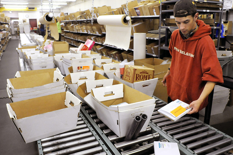 Distribution clerk Daniel Marsh fill orders to get them ready to ship on Monday at Group Publishing.