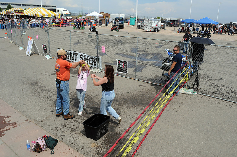 Bob and Judy Ikola of Bailey have a water balloon fight with their daughter Jackie, 11, on Sunday during the Suicidal Lifestyles motorcycle stunt show at the Thunder in the Rockies motorcycle rally.