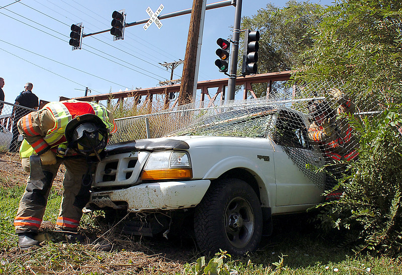 Loveland firefighters Shelby Vrem, left, and Cliff Shuffler try to get the horn to stop blowing on a pickup that smashed through a fence and into a garden in the 800 block of North Madison Avenue in Loveland on Thursday, Sept. 17, 2009.