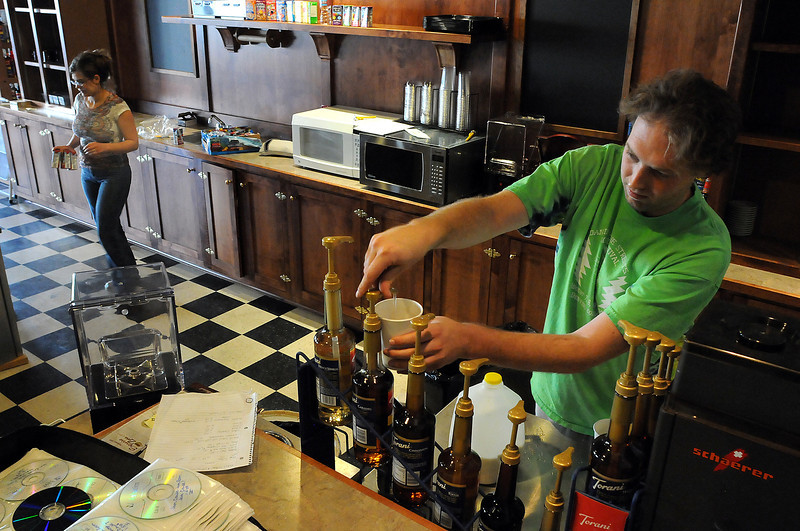 Alex Zoll, right, makes drinks for he and his wife Aryn, left, as they stock the espresso bar at the new Mandolin Cafe on Fourth Street in downtown Loveland. The cafe, which opens Oct. 1, will offer a full espresso bar, ice cream, burritos, sandwiches soup and live music in a relaxed atmosphere in the old location of the Sweet Spot.