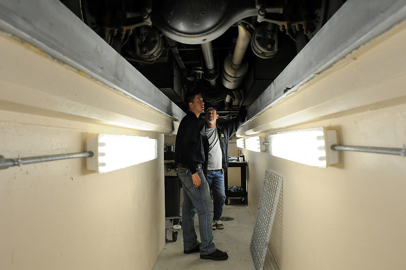 Lube technician Scott Megilligan, left, talks with Dave Schneider of the City of Loveland Fleet Maintenance under a school bus in a mechanics well on Monday at the new Thompson School District Transportation Center at 2500 East 13th Street. The new facility will allow most of the maintenance to be done in house instead of at the City Shops as before.