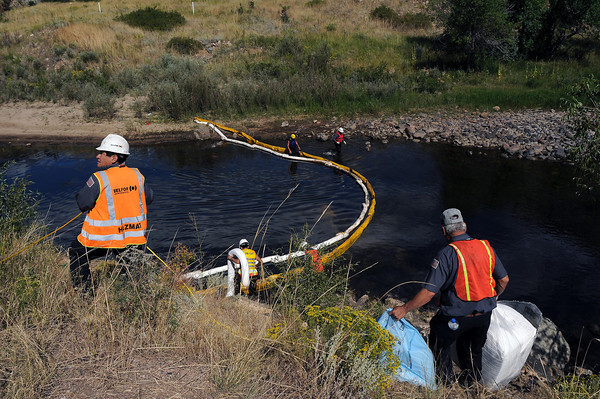 Emergency crews work the scene where a tanker crashed into the Cache la Poudre River and spilled nearly all of its 6,700 gallon capacity of asphalt and most of its 120 gallon diesel fuel into the river on Thursday.