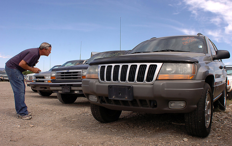 Chip Jansma, owner of Loveland Auto Salvage, takes inventory information Thursday from a row of vehicles on his lot that were part of  the Cash for Clunkers program.