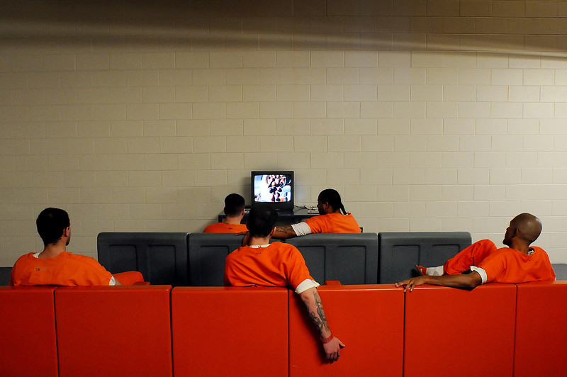Inmates pass the time watching daytime television on Wednesday at the Larimer County Detention Center in Fort Collins.