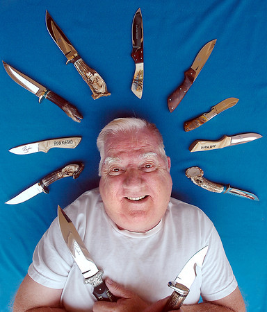 Bob Dill poses for a portrait Tuesday showing off some of the custom knives he has made at his Loveland home.