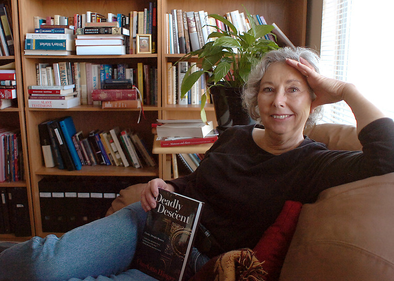 "Charlotte Hinger sits in her Loveland home office with her newest book, ""Deadly Descent."""