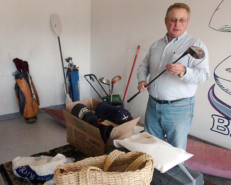 Steve Moore, president of the Big Thompson Kiwanis Club, prices items Friday for a garage sale to benefit Dr. Bob Grosboll who has treated patients in Loveland for four decades.