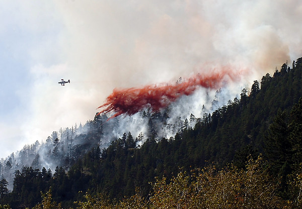 An airplane drops fire retardant on a 30-acre wildfire Tuesday, Sept. 8, 2009, on Triangle Mountain west of Loveland.