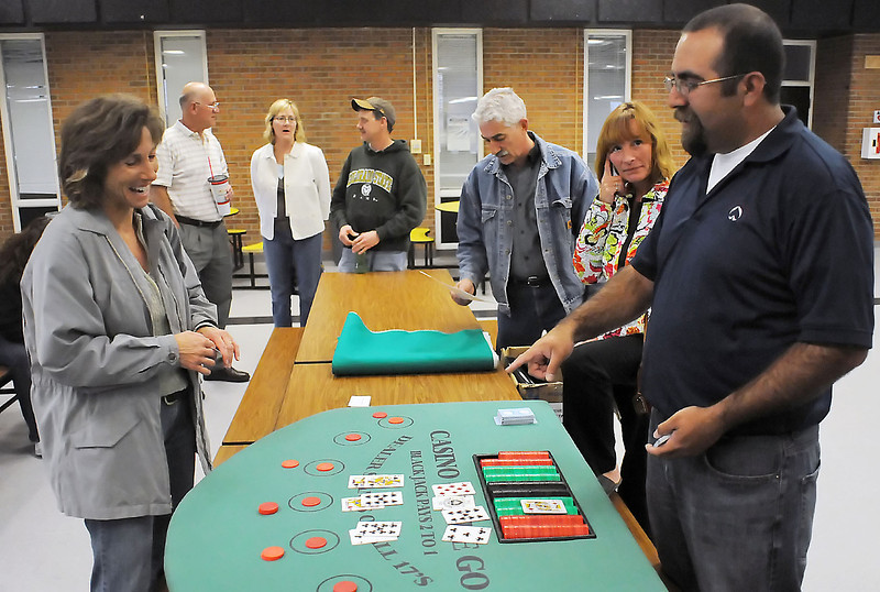 Jacob Mizer, right, answers a blackjack dealing question for Michele Stumbaugh, left, during dealer and casino training for parents who will be volunteering at one of the upcoming prom-a-rama events at area high schools. Mizer owns Casino On The Go and volunteered to teach parents how to run various casino games which will be offered for entertainment at the events that will also include air brush tattoos, a Velcro wall, video games, a silly photo booth and a live rock band.