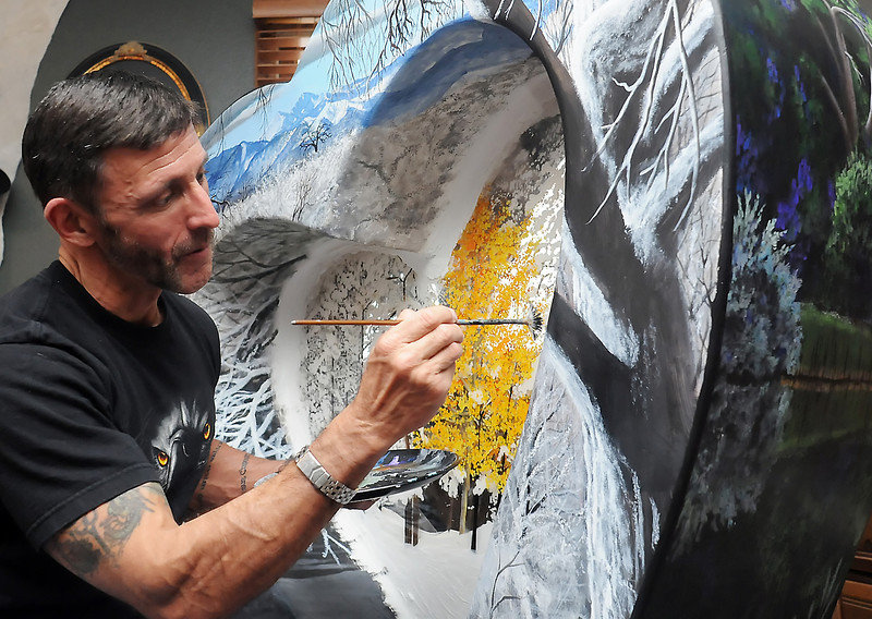 Loveland artist Ross Lampshire works on a painted heart recently at his home. The painting features Longs Peak and other mountains along the front range and will be placed at The Group Realty in Loveland.