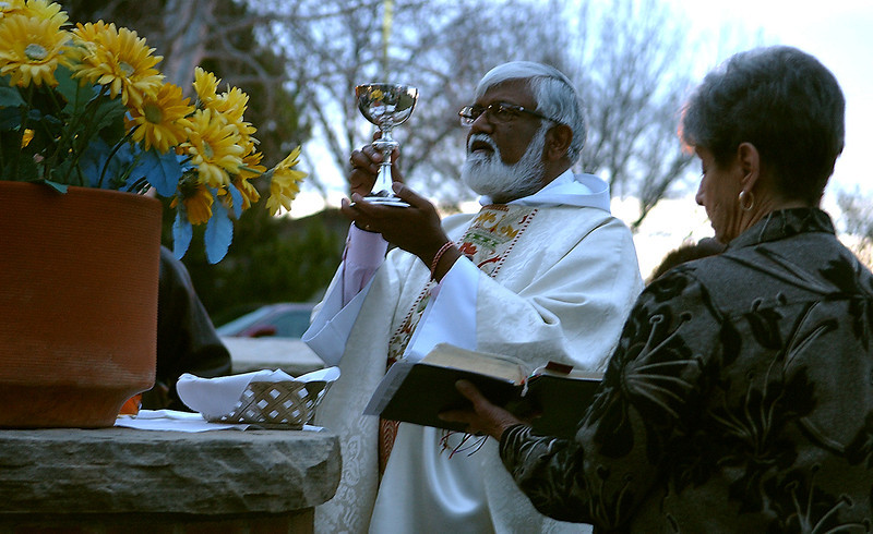 Lay Reader and Chalice Bearer Joyce Moore holds a hymnal open for Father Sathi Bunyan as he blesses the communion wine.  The two took the congregation outside Easter morning for a sunrise service.