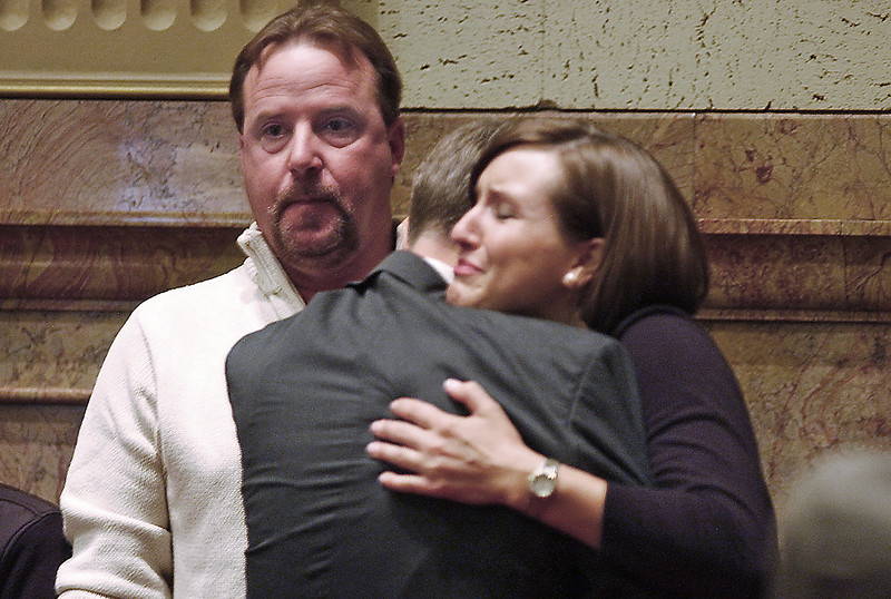 Greg Bauer stares listlessly into the Senate Chamber, thinking of his recently deceased son, Justin Bauer, who died serving his country.  Beside him, Kari Bauer, Justin Bauer's widow, grasps Sen. Kevin Lundberg in gratitude and sorrow as Lundberg has just passed a Resolution through the Senate designating part of State Highway 56 as a memorial to her late husband.