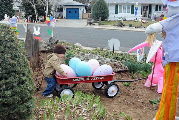 Finn Richter, 2, plays with an oversized Easter egg decoration in his neighbor's yard at 1125 W. 6th St., which belongs to John and Dorothy Rust. Several houses on the block have elaborate Easter-themed decorations each year that the residents of the neighborhood refer to as Easter Alley.