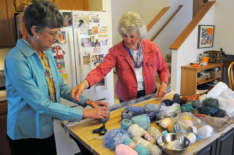 Ginny Crawford, left, and Mary Anne Ellison make a scarf together at Crawford's Loveland home on Wednesday, April 21, 2010. The women then sell the handmade scarves to raise money for various charities through their nonprofit called Strings from the Heart.