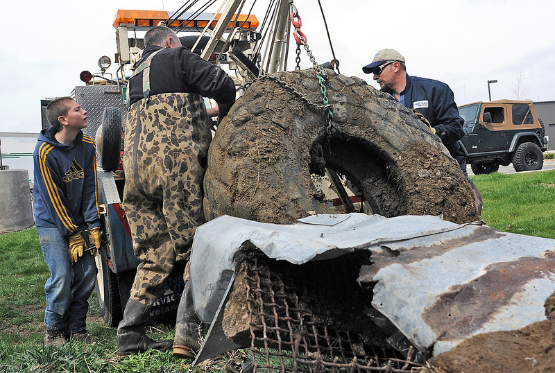 Hayden Barthlama, 12, left, works the tow truck controls while hoisting up a large tire and other debris with his father, Sheldon Barthlama, right, and Eddie Householder while volunteering to remove trash along the feeder canal between Dry Creek and Lake Loveland during Saturday's spring cleanup.