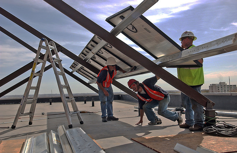 Kevin Studley ducks under the solar panels he helps to install, Wednesday, while Hill Slothower, left, and Mitch Whitten, right, team up with him.