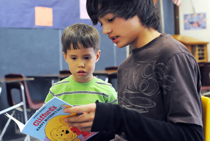 Four-year-old Rocky Clements listens as Conrad Ball Middle School seventh grader Lucas Wilson, 13, reads aloud to him Tuesday evening during the Reading is Fun Family Night event.
