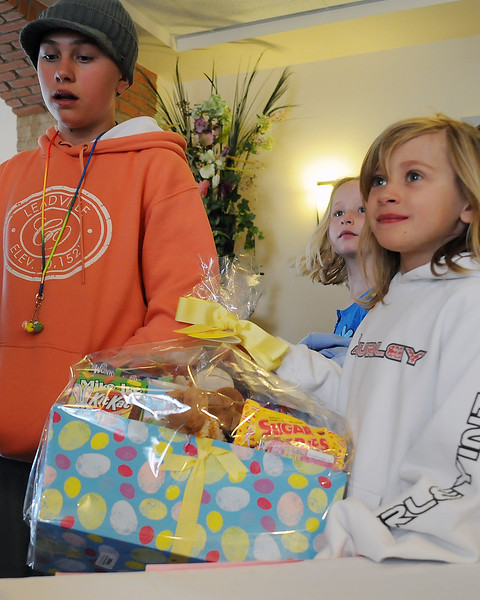 Genna Stobbe, 7, right, hoists an Easter basket full of goodies she won durig an Easter egg hunt at The Hillcrest on Saturday morning as she stands with her sister, Kailee Stobbe, 11, left, and cousin, Maya Stobbe, 6.