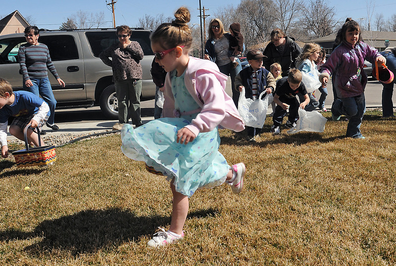 Four-year-old Faith Turner of Loveland, front, dashes around the lawn with her Easter basket while she and other youngsters look for hidden eggs during an Easter egg hunt Saturday at The Hillcrest, 535 N. Douglas Ave.