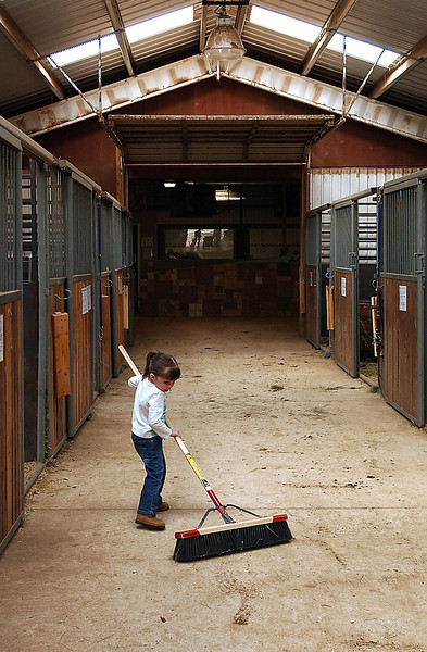 Kamryn Adent, age 4, works to clean the entire length of the passageway during her volunteer time at Hearts for Horses on Wednesday.