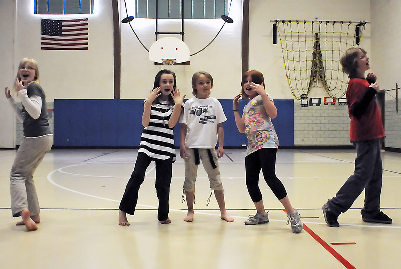 "Truscott Elementary School Odyssey of the Mind teammates work on their long-term solution problem Tuesday in the school's gymnasium by singing and dancing to the Elvis Presley song ""Hunk of burning love."" From left are fourth graders Emme Janssen, 9, Anna Bashford, 9, Remi Clarke, 9, Izze Johnson, 10, and Kaelan Ramirez, 10."