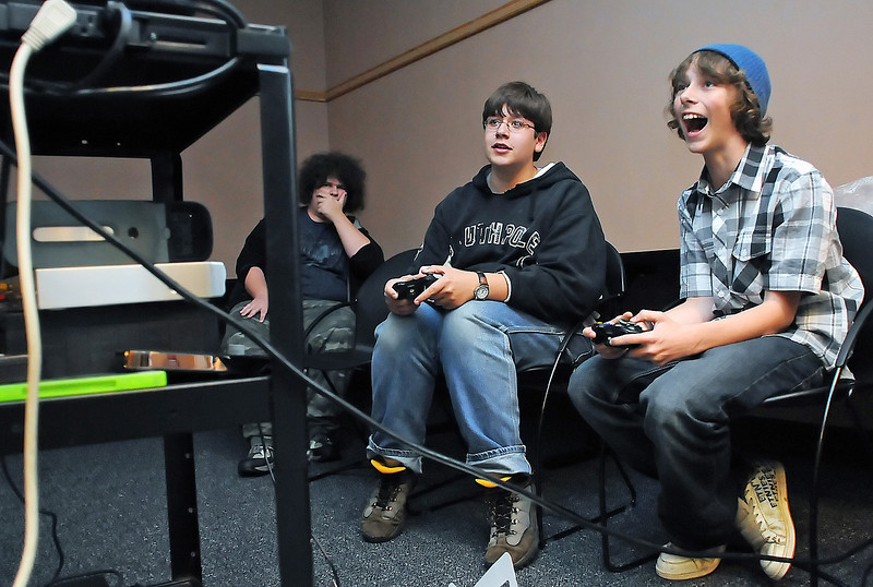 Tyler Cody, 15, right, plays a video game against Morgan Cook, 14, while Christopher Frey, 17, looks on during Teen Game Night at the Loveland Public Library on Friday. The once-a-month event features a variety of different video and board games for the teens to play as well as pizza and other treats for them to snack on. The upcoming library expansion will include a larger section for teens with study rooms, computers and a soundproof enclosed space.