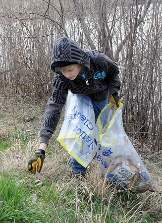 Tyler Benke, 15, reaches for a piece of trash at Jayhawker Ponds while volunteering for the annual spring cleanup with other Thompson Valley High School students on Saturday morning.