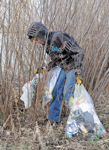 Tyler Benke, 15, picks up trash along the water's edge at Jayhawker Ponds on Saturday morning while volunteering with other students from Thompson Valley High School for the spring cleanup.