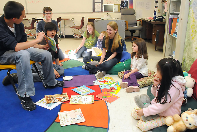 Conrad Ball Middle School seventh grader Julian Von Holten, 13, left, reads a book aloud during the Reading is Fun event where middle school students lead a variety of activities to get preschoolers enthusiastic about reading. Clockwise from left are Julian, Lucas Wilson, 13, David Leach, 14, Madison West, 11, Sarah West, 4, Caroline Foster, 13, Sienna Hunsinger, 4, and Daniela Sanchez, 5.