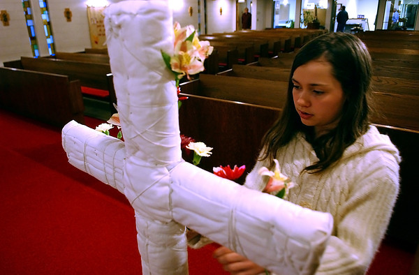 Lindsey Ranz, 10, decorates a cross with flowers in the All Saints' Epsicopal Church, Sunday, as part of a children's involvement activity for Easter.