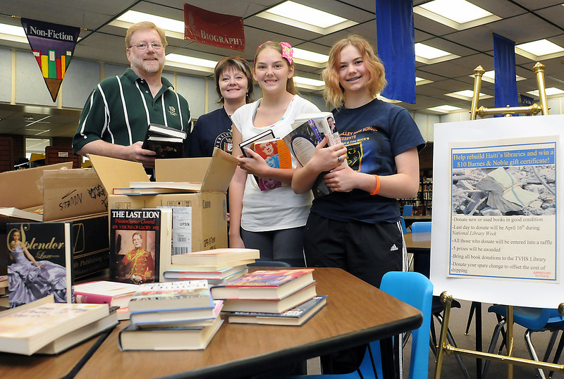Thompson Valley High School volunteers who helped collect 12 boxes of books to support the building of libraries in Haiti pose in the school's library with some of the donated books. From left are principal Mark Johnson, media specialist Jake Pettit, freshman Amanda Jacobs, 14, and sophomore Laurel McKee, 15. The books will be sold and the proceeds will help rebuild libraries that were damaged in the recent earthquake that ravaged the country.