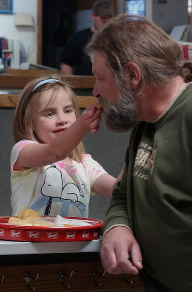 Austin Acres, 7, shares a cheesy nacho with her grandfather, Mark Acres, Sunday, at Sweetheart Lanes.  Acres' family and friends came out to the bowling benefit in support of her recent heart surgery.