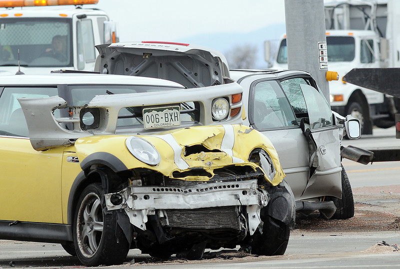 Two vehicles that collided Wednesday afternoon at US Highway 287 and Colorado 56 rest in the intersection as tow trucks arrive to remove them from the scene.